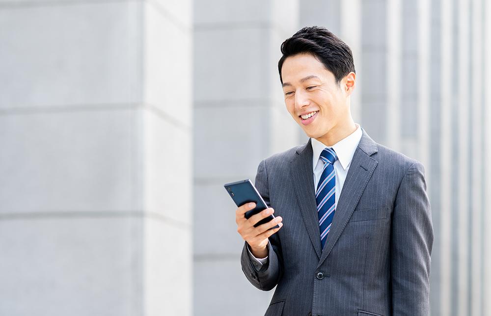 スマートフォンを見てほほ笑むビジネスマン
