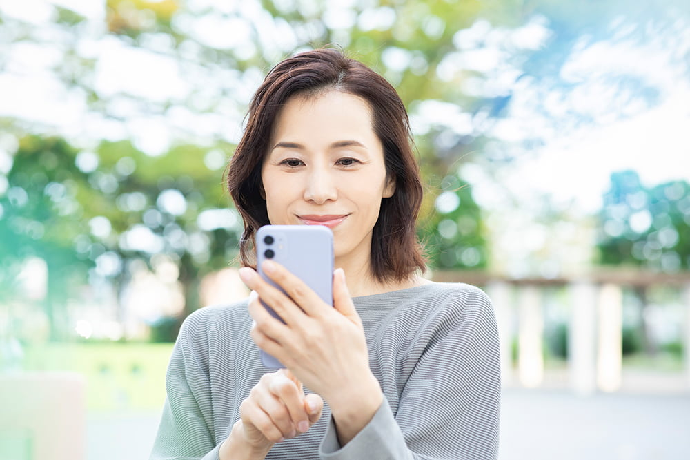 野外でスマートフォンを操作する女性
