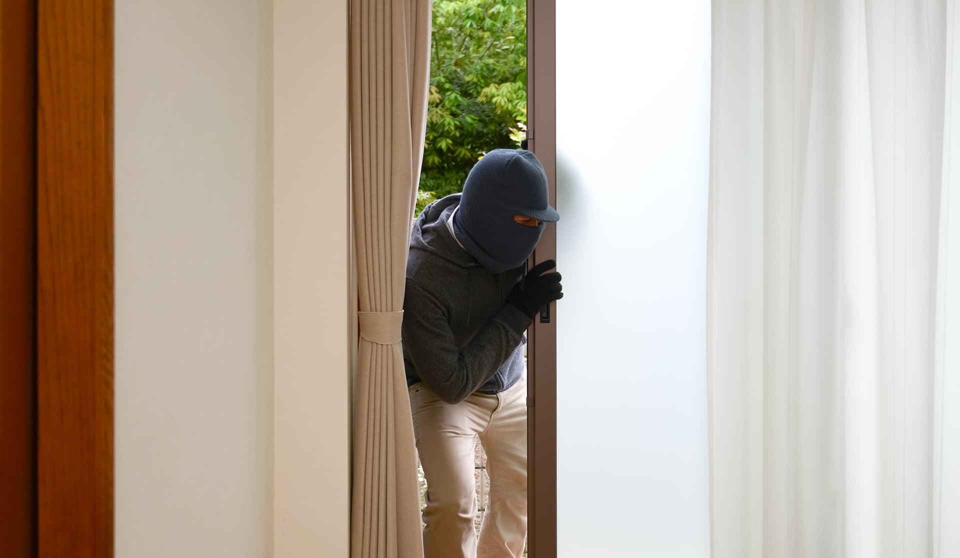 中を伺い、窓から侵入する男性