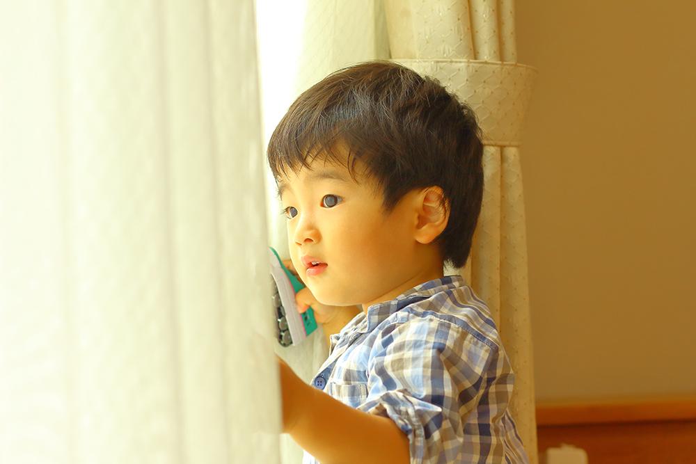 おもちゃを持ちながらカーテン越しで外を見る男の子